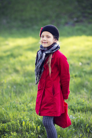 checkered scarf: girl in red raincoat and checkered scarf on green spring meadow