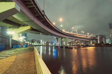 hanged: empty embankment with hanged highway structure by night at Sumida river in Tokyo, Japan Stock Photo