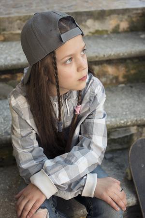 peaked: urban girl  in peaked gray cap sit on stairs