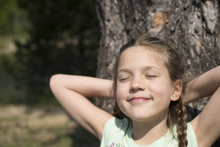 huge tree: happy child girl sunbathing with closed eyes near huge tree Stock Photo