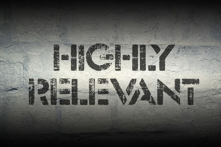 highly: highly relevant stencil print on the grunge white brick wall