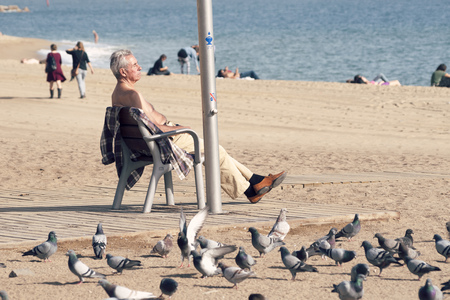 rest day: BARCELONA - NOVEMBER 16, 2009 :man take a rest by sunny autumn day on famous Barcelonetta beach on November 16, 2009 in Barcelona, Spain.