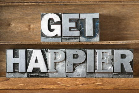 happier: get happier phrase made from metallic letterpress type on wooden tray