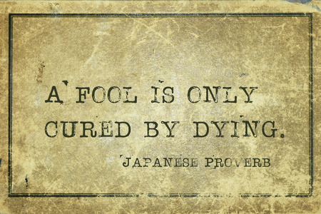 cardboard only: A fool is only cured by dying - ancient Japanese proverb printed on grunge vintage cardboard Stock Photo