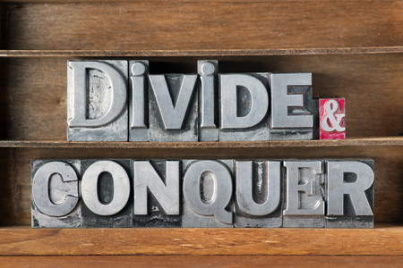 divide and conquer phrase made from metallic letterpress type on wooden tray