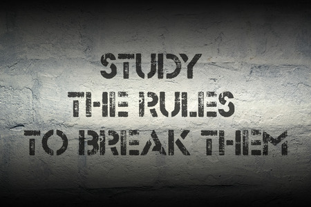 break the rules: study the rules to break them stencil print on the grunge white brick wall Stock Photo