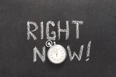 right now exclamation handwritten on chalkboard with vintage precise stopwatch used instead of O