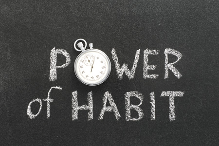 power of habit phrase handwritten on chalkboard with vintage precise stopwatch used instead of O