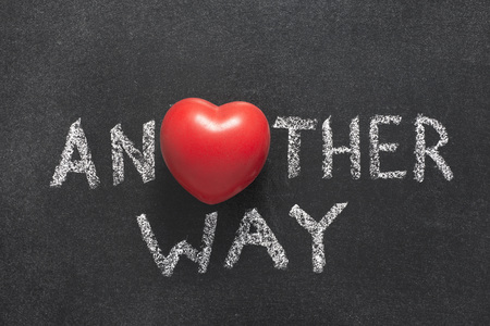 another way: another way phrase handwritten on blackboard with heart symbol instead of O Stock Photo