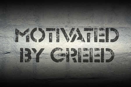 greed: motivated by greed stencil print on the grunge white brick wall