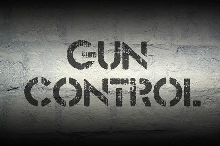 gun control: gun control stencil print on the grunge white brick wall Stock Photo