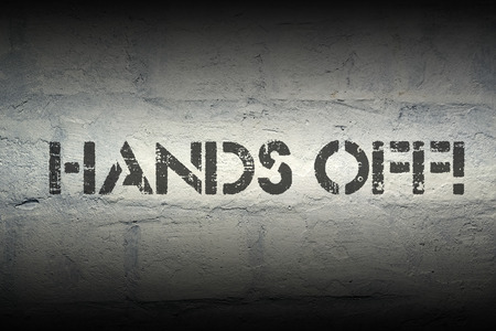 hands off: hands off exclamation stencil print on the grunge white brick wall