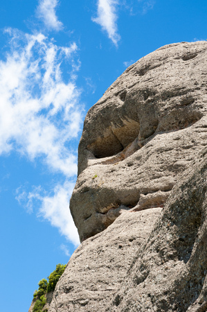huge: huge weathered rock with blue sky behind Stock Photo