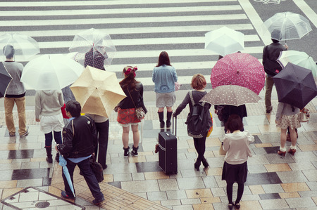 omotesando: TOKYO - APRIL 23: colorful people crowd waiting on the street crossing under the rain in Omote-sando district on April 23, 2011 in Tokyo, Japan.