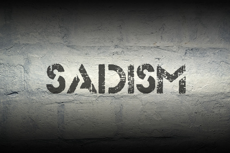 perversion: sadism word stencil print on the grunge white brick wall Stock Photo