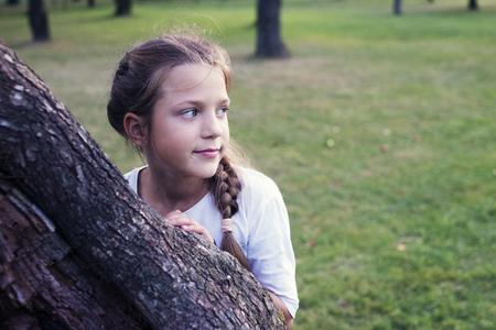 huge tree: girl behind huge tree in evening garden