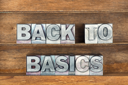 basics: back to basics phrase made from metallic letterpress type on wooden tray