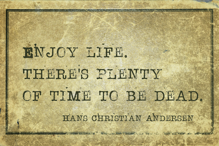 ancient philosophy: Enjoy life. Theres plenty of time to be dead - famous Danish fairy tale writer Hans Christian Andersen quote printed on grunge vintage cardboard Stock Photo