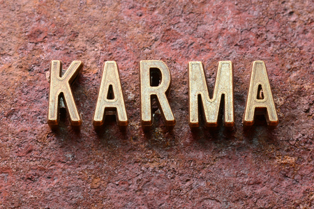 karma: karma word made from metallic letters on red rusty surface