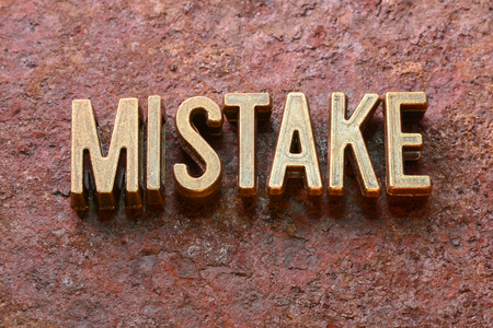 flaw: mistake word made from metallic letters on red rusty surface