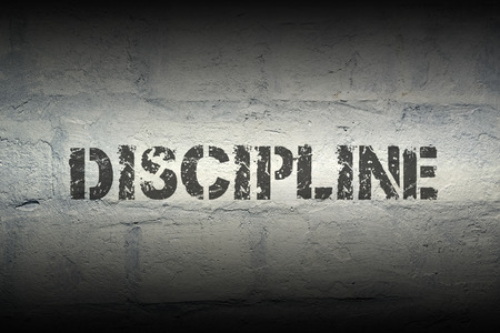 discipline word black stencil print on the grunge brick wall with gradient effect