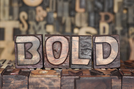bold word made from wooden letterpress blocks on many different letters background