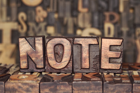 NOTE word made from wooden letterpress blocks on many different letters background