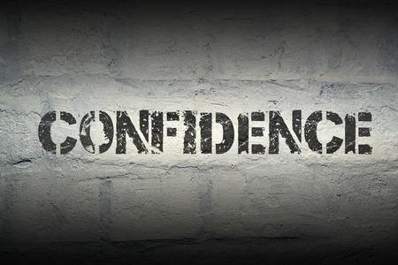 trait: confidence stencil print on the grunge white brick wall Stock Photo