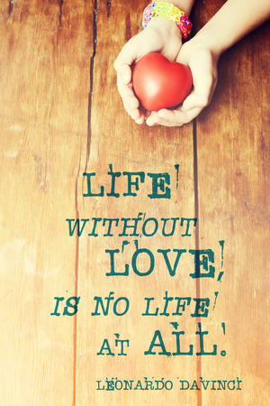 leonardo da vinci: famous Leonardo Da Vinci quote about life without love printed over image with red heart in hands Stock Photo