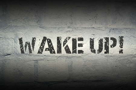 wake up exclamation stencil print on the grunge white brick wall