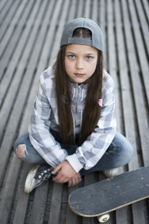 serious child girl with skateboard sitting on wooden deck  Stock Photo