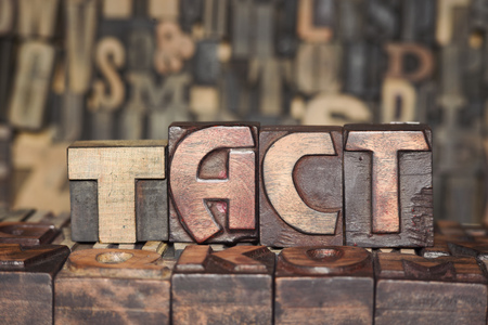 at tact: TACT word made from wooden letterpress blocks on many different letters background