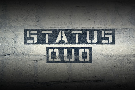 status quo stencil print on the grunge white brick wall