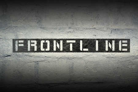 frontline: frontline stencil print on the grunge white brick wall