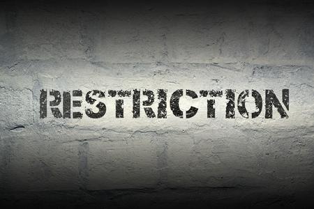 restriction stencil print on the grunge white brick wall Фото со стока
