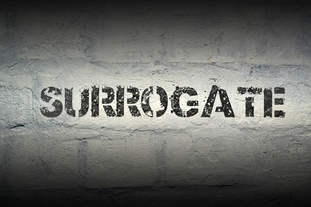 surrogate: surrogate stencil print on the grunge white brick wall Stock Photo