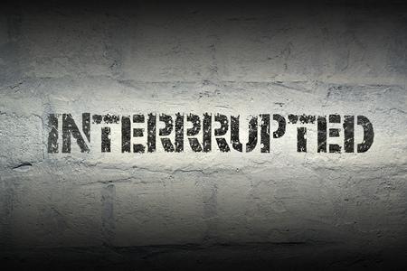 interrupted stencil print on the grunge white brick wall Фото со стока