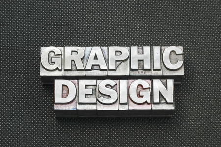 letterpress blocks: graphic design phrase made from metallic letterpress blocks on black perforated surface Stock Photo