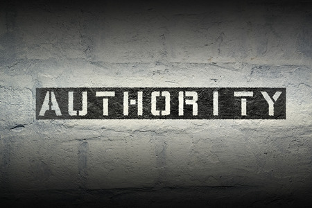 autoridad: authority stencil print on the grunge white brick wall