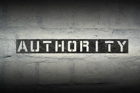 impression au pochoir autorité sur le mur de briques blanches de grunge Banque d'images