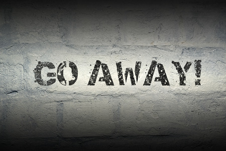 go away exclamation stencil print on the grunge brick wall with gradient effect Фото со стока