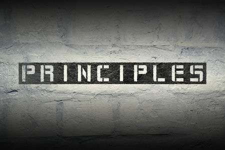 principles: principles stencil print on the grunge white brick wall