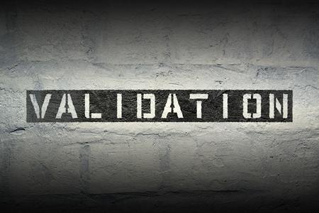 validation: validation stencil print on the grunge white brick wall