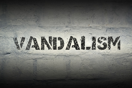 vandalism: vandalism stencil print on the grunge white brick wall Stock Photo