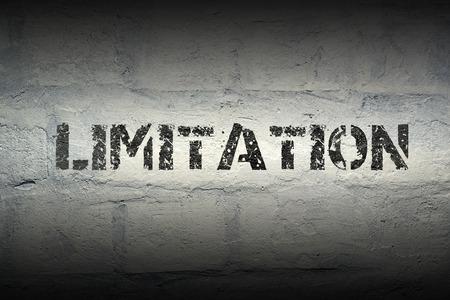 delimitation: limitation stencil print on the grunge white brick wall