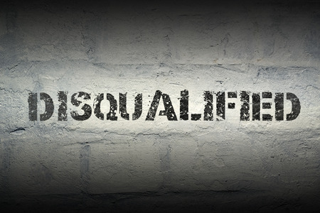 disqualified stencil print on the grunge white brick wall Stok Fotoğraf