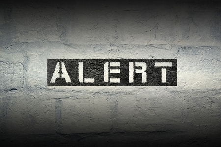alert red stencil print on the grunge white brick wall