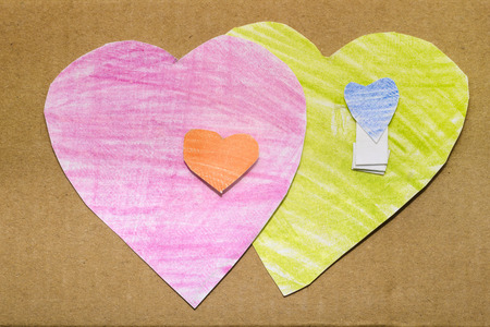 two simple paper hearts painted by pink and green pencil isolated on white