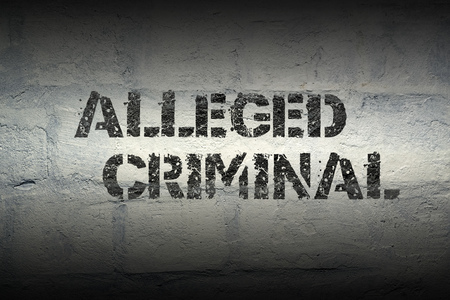 alleged: alleged criminal stencil print on the grunge white brick wall Stock Photo