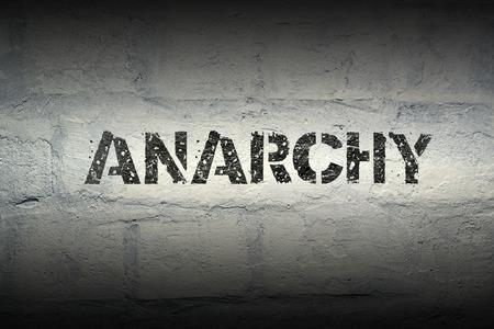 anarchism: anarchy stencil print on the grunge white brick wall